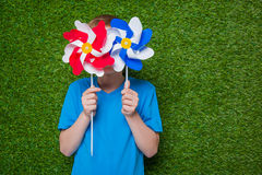 Boy hiding behind pinwheels over grass Stock Images