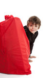 Boy hiding behind Santa sack Stock Photos