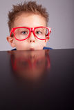 Boy hiding behind a table Royalty Free Stock Image