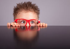 Boy hiding behind a table stock images