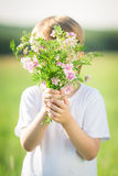 Boy hiding by bouquet. Of spring flowers. Mother`s day concept Royalty Free Stock Photo