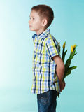 Boy hiding bouquet of flowers behind itself. Holiday mother's day concept. Little boy has prepared surprise present for mum, flowers yellow tulips, holds it Stock Image