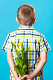 Boy hiding bouquet of flowers behind itself. Holiday mother's day concept. Little boy has prepared surprise present for mum, flowers yellow tulips, holds it Royalty Free Stock Photography