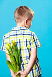 Boy hiding bouquet of flowers behind itself. Holiday mother's day concept. Little boy has prepared surprise present for mum, flowers yellow tulips, holds it Stock Photo