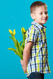 Boy hiding bouquet of flowers behind itself. Holiday mother's day concept. Little boy has prepared surprise present for mum, flowers yellow tulips, holds it Royalty Free Stock Photos