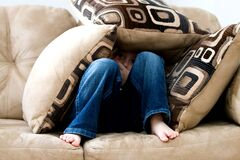 Boy hiding in couch cushions