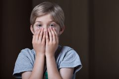 Boy hiding face behind hands Royalty Free Stock Image