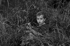 Boy hiding in the grass Stock Image