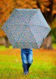 Boy hiding himself behind the umbrella Stock Image