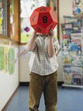 Boy Hiding His Face With Ball Stock Images
