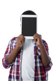 Boy hiding his face behind digital tablet Stock Image