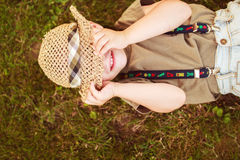Boy hiding his face with his hat Stock Images