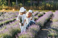 Boy hiding lavender behind his back. Little boy giving a bouquet of flowers to his mom. Motherhood Love Care Concept. Mother and a cute little son hugging and stock photo