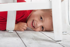Boy hiding. Little boy hiding under chair waiting for Santa Stock Image