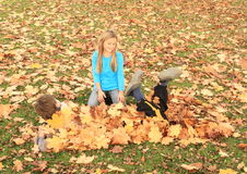 Boy hiding under leaves. Little boy in lying and hiding under fallen maple leaves covered by a girl stock images