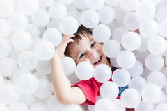 Boy hiding under white balls at the playground Royalty Free Stock Images