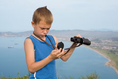 Boy hiker with binoculars on top of mountain. Royalty Free Stock Images