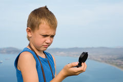 Boy hiker looking at the compass being on top of mountain. Royalty Free Stock Photography