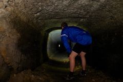 Boy hiker - mountainbiker in a sabdstone cave or dry water channel. Visiting of underground Stock Image