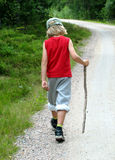 Boy hiking. Boy walking during hike, with a stick Royalty Free Stock Photos