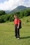 Boy hiking in countryside. Boy with rucksack hiking in green countryside with mountains in background Royalty Free Stock Image
