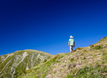 Boy hiking into the mountains Royalty Free Stock Images