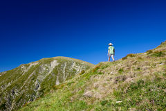 Boy hiking into the mountains Royalty Free Stock Photos