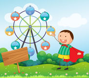 A boy in the hill with a wooden signboard  and a ferris wheel at Stock Images