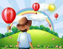 A boy at the hilltop with flying balloons and a rainbow Stock Images