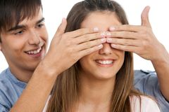 Boy hinding girls eyes with hands. Royalty Free Stock Photography