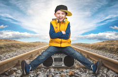 The boy in Hip-Hop sits on the railway and listening to vintage tape recorder. Royalty Free Stock Photos