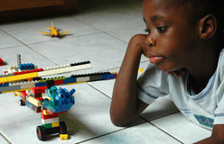 Boy and his aircraft creation. Boy looks at his building block airplane with some discouragement stock images
