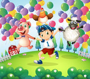 A boy and his animals at the farm with floating balloons Stock Photography