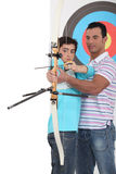 Boy with archery coach Royalty Free Stock Image