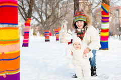 Boy and his baby sister walking between colorful decorated trees in a snowy park Royalty Free Stock Photo