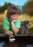 Boy and his beloved kitten playing with a boat from pier in pond Stock Image