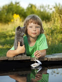 Boy and his beloved kitten playing with a boat from pier in pond Stock Photos