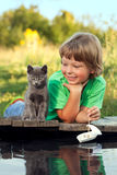 Boy and his beloved kitten. Playing with a boat from pier in a pond summer evening Stock Image