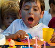Boy in his birthday. Boy with painted face blowing the candles of its cake of birthday Stock Images