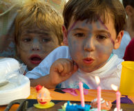 Boy in his birthday. Boy with painted face blowing the candles of its cake of birthday Royalty Free Stock Photography