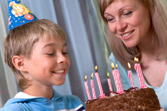 Boy in his birthday. Mum and son party in hats, pie with candles Stock Image