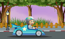 A boy in his blue racing car with a white star Stock Photo