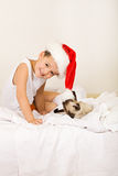 Boy with his cat waiting for christmas. Boy in santa hat playing with his cat, waiting for christmas Royalty Free Stock Image