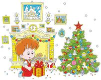 Boy with his Christmas gift. Vector illustration of a little boy sitting with his holiday gift near a fireplace and a colorfully decorated Christmas tree Royalty Free Stock Image