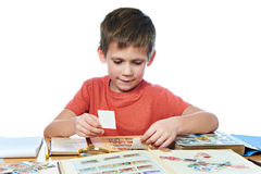 Boy with his collection of old postage stamps isolated. White Stock Photo