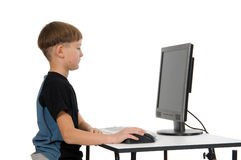 Boy on His Computer. Boy on computer with cordless mouse and keyboard royalty free stock images