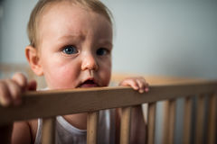 Boy in his crib. Cute blond baby boy with blue eyes staying in his crib, the child is happy and holds the crib`s edges Stock Photos