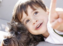 A boy and his dog. A young boy laying his head on his dog and pointing somthing out to the dog Stock Images