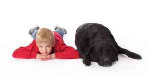 A boy and his dog 2. A boy lays on the floor next to a black lab Stock Image