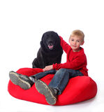 A boy and his dog. A young boy in red, on a red bean bag chair, with his arm around a black lab royalty free stock photos